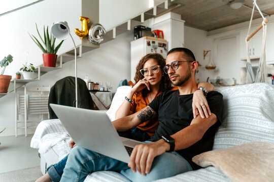 Concentrated young female in eyeglasses cuddling ethnic husband while watching movie together on laptop sitting on sofa at cozy home