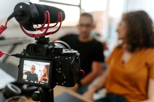 Professional camera with microphone on tripod recording video with unrecognizable man and woman during interview in studio