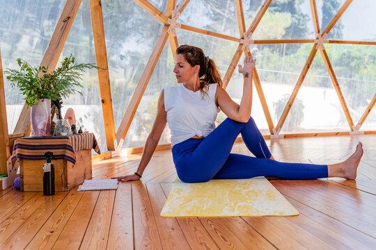 Anonymous flexible barefoot female sitting in marichi's pose on yoga mat on floor