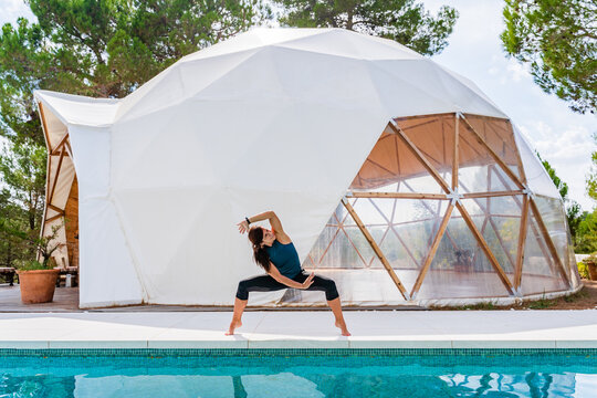 Unrecognizable fit female in sportswear standing with legs wide apart and raised arm near tent and swimming pool while practicing yoga
