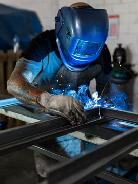 Unrecognizable male welder using welding machine on metal detail while working at workbench in factory