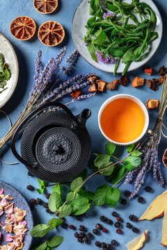 Herbal tea, natural, organic, and healthy. An overhead shot of a cup of tea with a tea pot and an assortment of ingredients, herbs, fruits and flowers