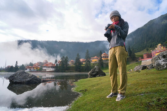 Low angle full body of anonymous tourist with photo camera taking photo of calm lake located in mountainous terrain and oriental shrine