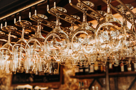 Low angle of shiny crystal glasses hanging on metal rack over bar counter