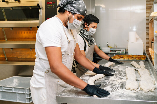 Selective focus of two latino bakers kneading dough for bread before putting it in the oven on a bakery table wearing black gloves and a face mask because of the 2020 covid19 coronavirus pandemic