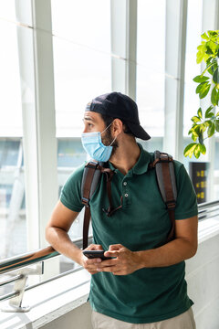 Side view of male tourist wearing medical mask standing in departure lounge of airport and browsing cellphone