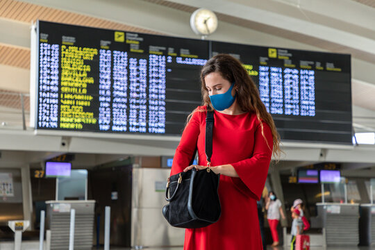 Female tourist wearing protective mask standing in airport against departure board and checking bag while waiting for flight during coronavirus epidemic