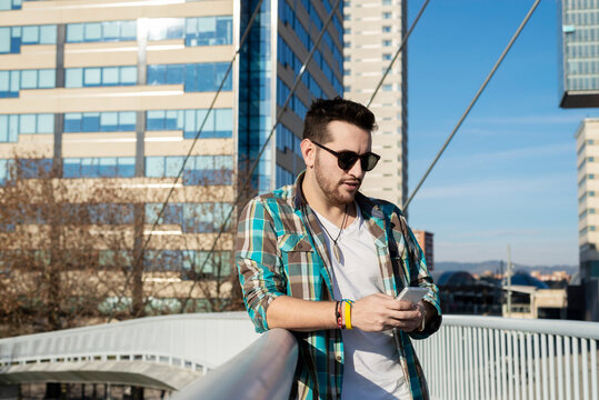 Focused young male in stylish outfit using contemporary mobile phone against modern building on sunny weather