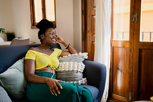 Positive young African American female in bright yellow shirt and transparent eyeglasses looking away with bright friendly toothy smile while relaxing on couch in bright studio apartment