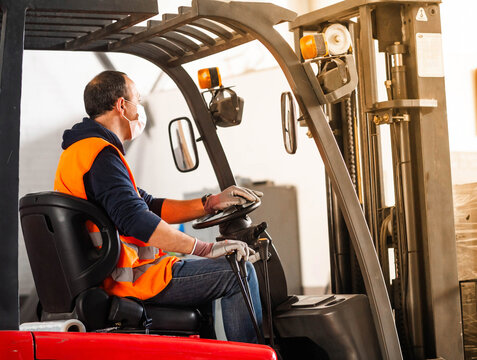 Side view unrecognizable male worker in high visibility vest and face mask driving autoloader machine while working in warehouse