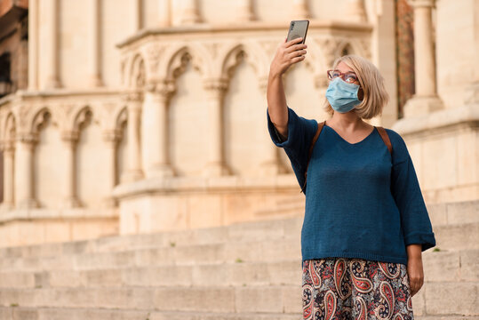 Side view of female traveler in medical mask for coronavirus prevention with smartphone standing on steps and taking pictures of exterior of medieval cathedral while visiting Cuenca town in Spain