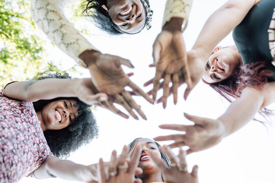 From below of group of multiracial cheerful women standing together and stacking hands in name of unity and friendship