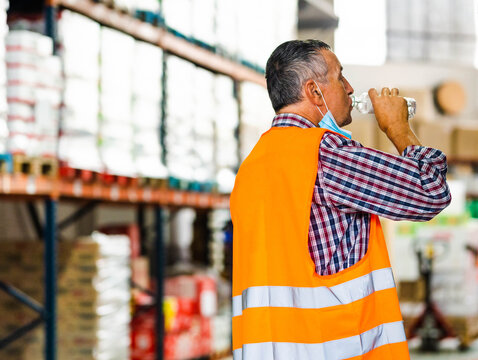 Side view adult male worker in orange high visibility vest and lowered mask drinking water from plastic bottle while standing near shelves in warehouse