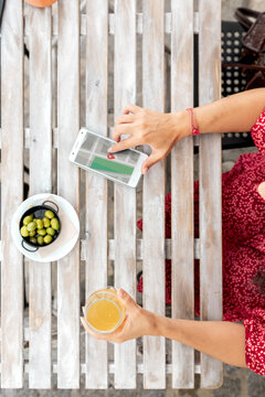 Top view of crop unrecognizable female with glass of refreshing drink touching screen on cellphone with map application while sitting at table with bowl of olives