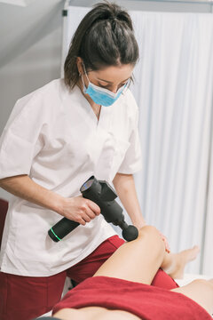 Female physiotherapist using massage gun on leg of patient during percussive therapy in modern hospital