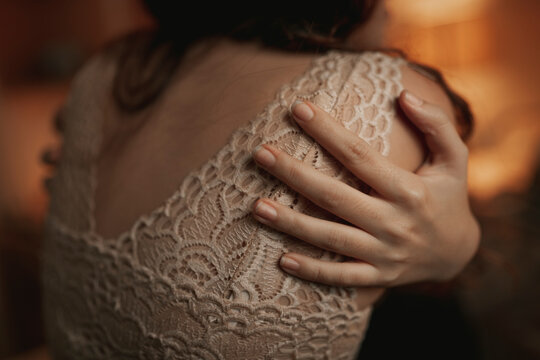 Back view of anonymous female in lace bra embracing herself while sitting in cozy room lit by dim orange light