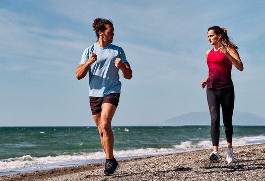 Sportsman and sportswoman in activewear running along sea on beach while doing cardio training and looking at each other