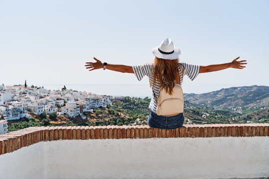 Back view of delighted female tourist sitting on stone border with outstretched arms and enjoying freedom on background of cityscape of Frigiliana during vacation in summer