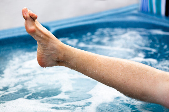 Female feet in hot tub with deformities- bunions and hammertoes. Horizontal.