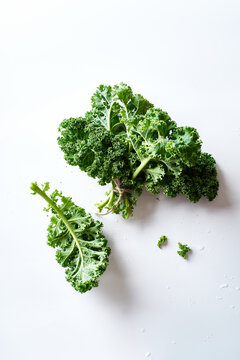 Green curvy kale leaves tied with twine on white background