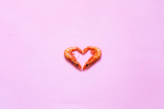 Raw prawns placed in shape of heart on bright pink background in studio