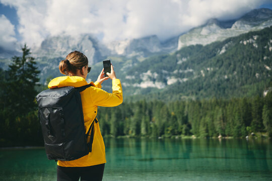 Back view of unrecognizable woman photographing high mountains on cellphone during trip in Dolomites