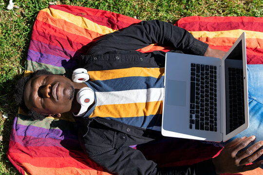 Top view of tired African American male freelancer lying on blanket with netbook in city and having nap during remote work on sunny day