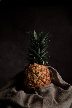 Still life composition with whole ripe pineapple wrapped in textile on wooden stand against black background
