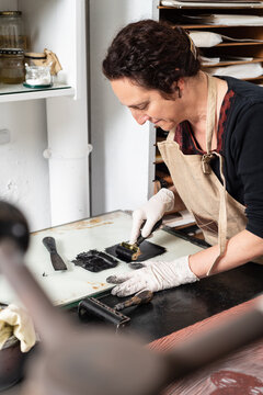 Female artisan in glove using braver and spreading ink on sheet for engraving while working in professional workshop