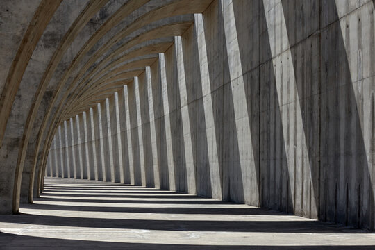 Columns of empty concrete walkway illuminated by sunlight casting lines of shadow on stone wall