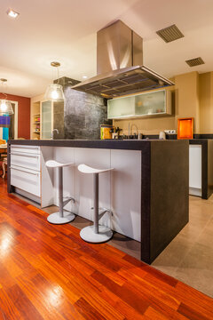 Contemporary kitchen with steel hood and bar counter lighted with bright lamps