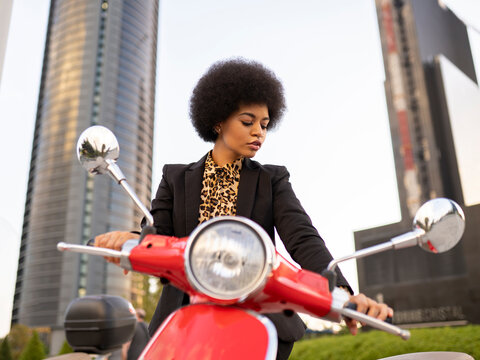 From below of confident African American female with motorcycle wearing black classic outfit looking down