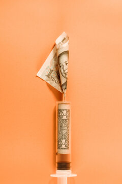 From above of plastic medical syringe with rolled one dollar bill and yuan banknote placed on orange background demonstrating currency exchange concept