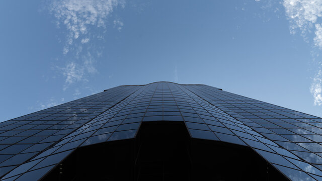 From below of futuristic skyscraper building made of glass windows located against blue sky in city center