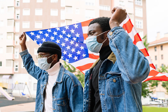 Low angle of cheerful African American male friends in masks standing with USA national flag on street and expressing joy