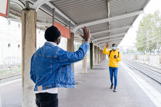 Black male friends in medical masks waving hands and greeting each other on train platform during coronavirus epidemic