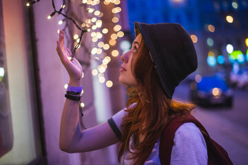 Side view of stylish hipster millennial woman in hat and with backpack touching glowing garland while standing near building in evening city Fotomurales