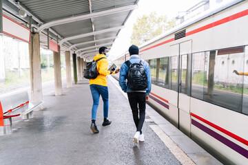 African American traveling males wearing protective masks walking along railway platform and talking before departure Fotobehang