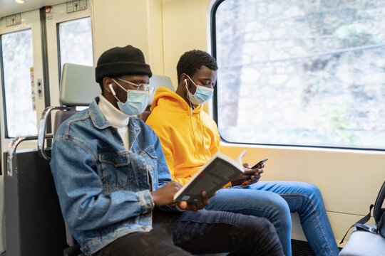 Busy African American male travelers in medical masks reading book and listening to music while sitting on passenger seats in train and entertaining during trip