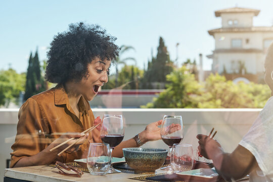 Side view of African American female friends sitting at table with sushi and wondering with opened mouth