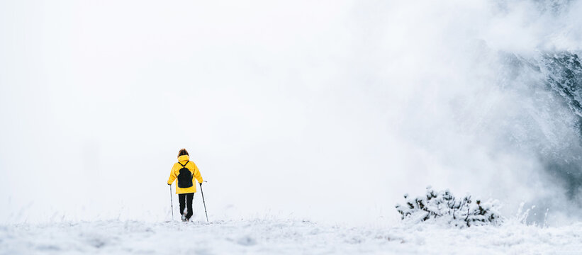 Back view of anonymous hiker with trekking poles walking on snowy ground in Pyrenees mountains in Andorra