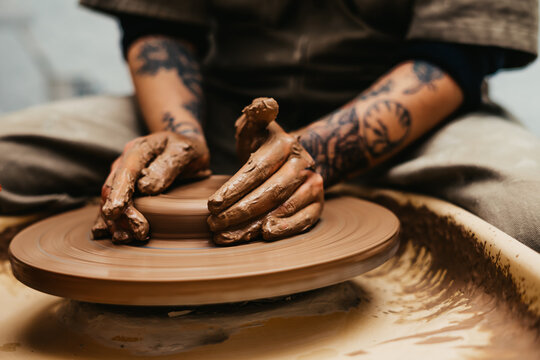 Closeup of dirty hands of anonymous craftsman using pottery wheel and making clay pot in workshop