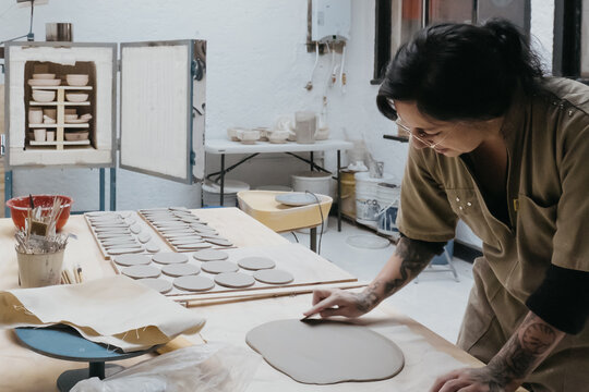 Artisan using sharp tool and making holes in piece of clay while creating handmade pottery in art studio
