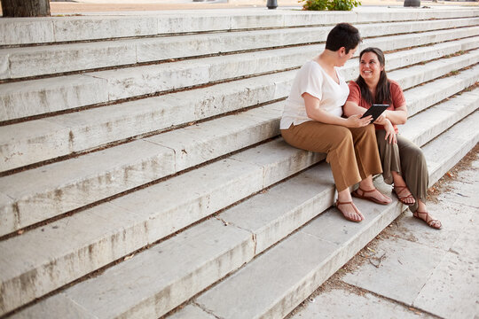 Positive homosexual woman sharing tablet with smiling partner while resting on shabby staircase in city