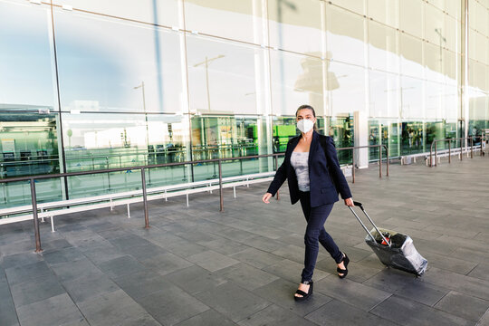 Cheerful female tourist in mask with suitcase and backpack walking in airport and smiling at camera while enjoying summer weekend