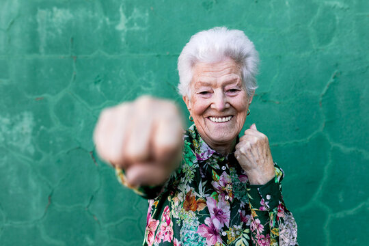 Cheerful elderly gray haired lady in stylish colorful blouse having fun and boxing at camera while standing against green wall