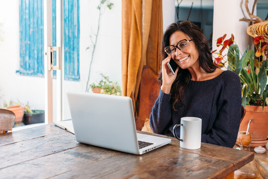 Positive adult ethnic female entrepreneur in casual wear talking on mobile phone and writing information in planner while standing near table with laptop and working remotely in cozy country house