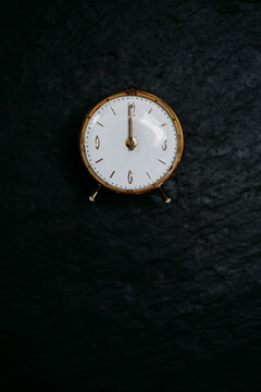 From above of retro round clock with yellow metal case on dial placed on black background
