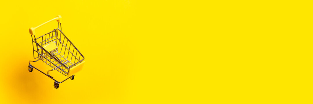 flying empty trolley on a bright yellow background. Close-up. Banner.