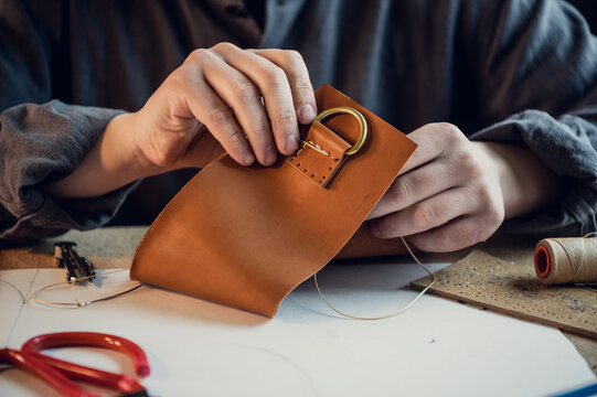 A young shoemaker manually sews decorative elements to leather shoes in the workshop.